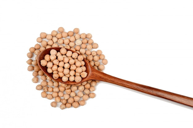 Uncooked chickpeas on wooden spoon