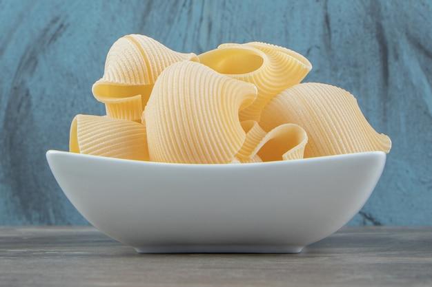 Сырые макароны конкильи в белой миске.