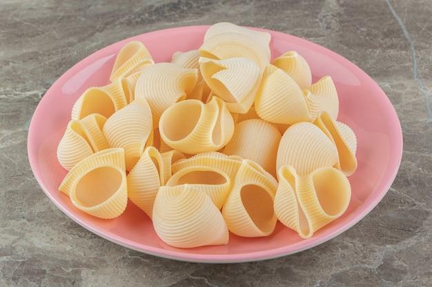 Сырые макароны конкильи на розовой тарелке.
