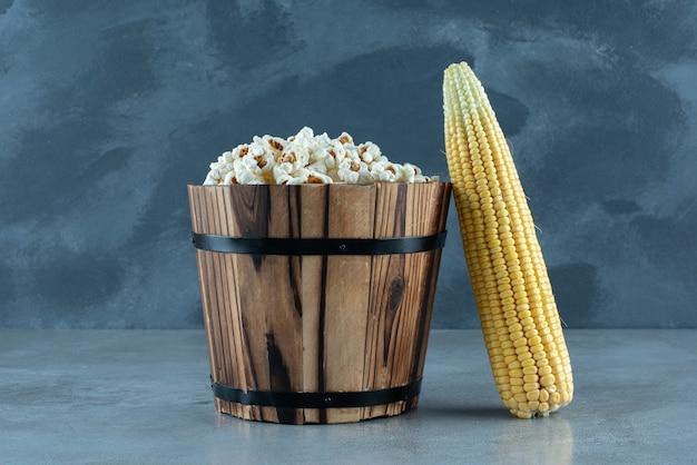 Pianta di mais cruda con popcorn bianchi intorno. foto di alta qualità