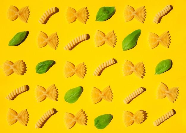 Сырые фигурные макароны и узор из листьев базилика на желтой поверхности.