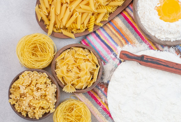 Uncooked different types of pasta with flour and raw egg on a tablecloth.