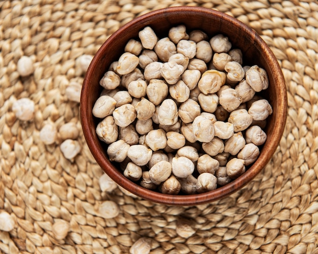 Uncooked dried chickpeas in bowl on a straw mat