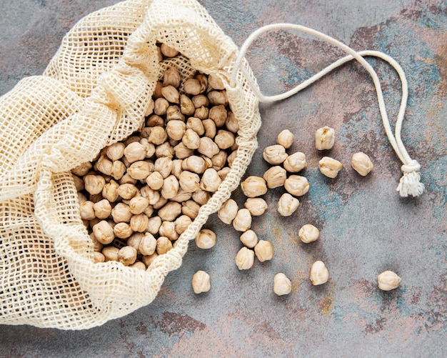 Uncooked dried chickpeas in cotton bag on a grey concrete background