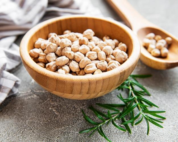 灰色のコンクリートの表面にボウルに入れた未調理の乾燥ひよこ豆