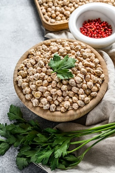 木製ボウルに未調理の乾燥ひよこ豆。灰色の背景。上面図