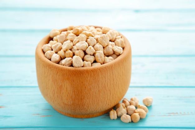 青い木製の背景に木製のボウルに未調理の乾燥ひよこ豆。