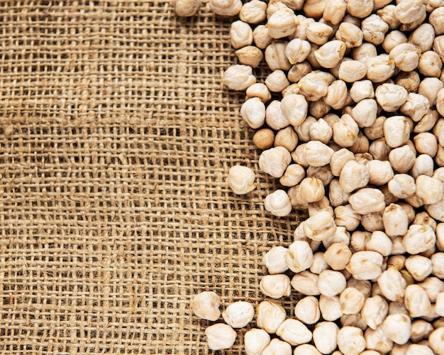 Uncooked dried chickpeas on a old burlap background