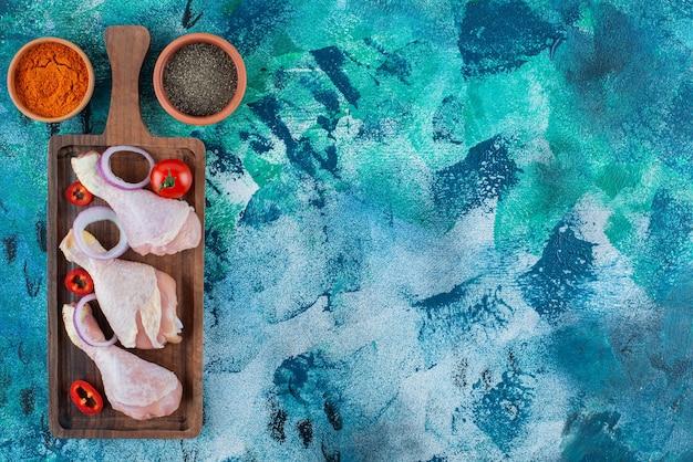 青の背景に、ボード上の未調理のドラムスティックと野菜。
