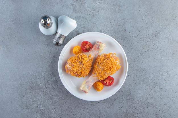 Сырые голени на тарелке рядом с солью на мраморной поверхности.