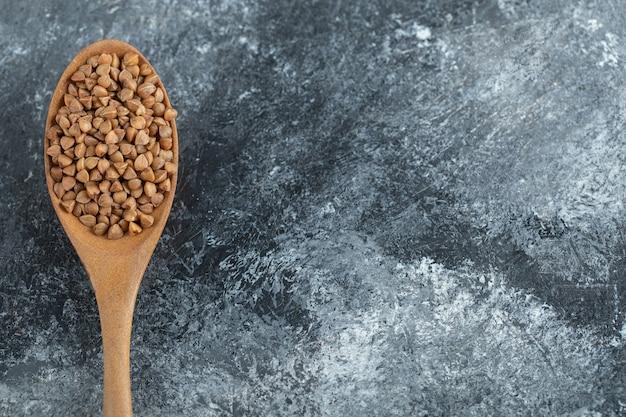 Сырая сухая гречка на деревянной ложке
