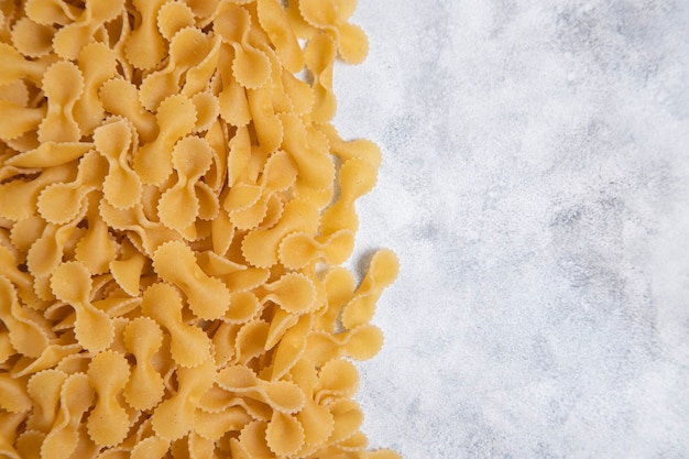 요리하지 않은 건조 farfalle 파스타를 대리석 테이블 위에 놓았습니다. 고품질 사진