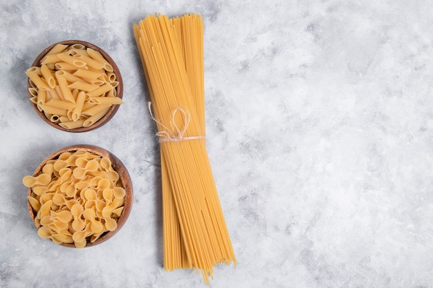 Uncooked dry pasta placed on a marble background . high quality photo