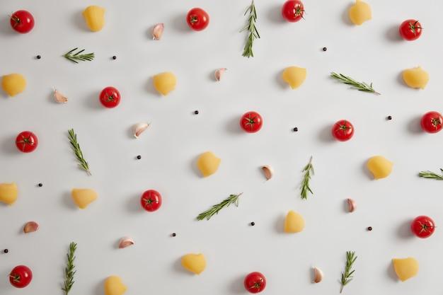 조리하지 않은 건조 전체 파스타 껍질과 신선한 재료 붉은 토마토, 후추, 로즈마리. 전통적인 이탈리아 파스타에 대한 최고의 레시피를 시도합니다. 흰 바탕. 위에서 봅니다. 플랫 레이 구성