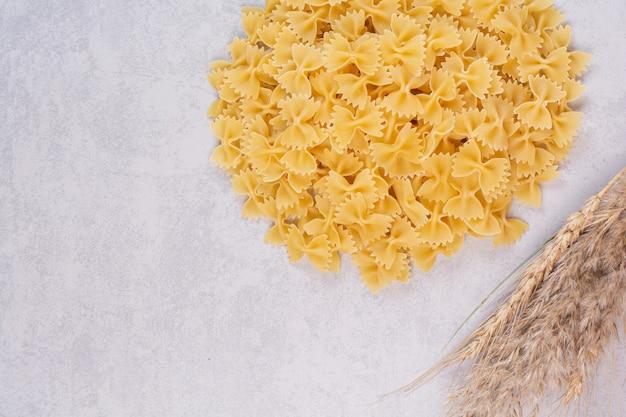 Сырые макароны фарфалле на белой поверхности с пшеницей