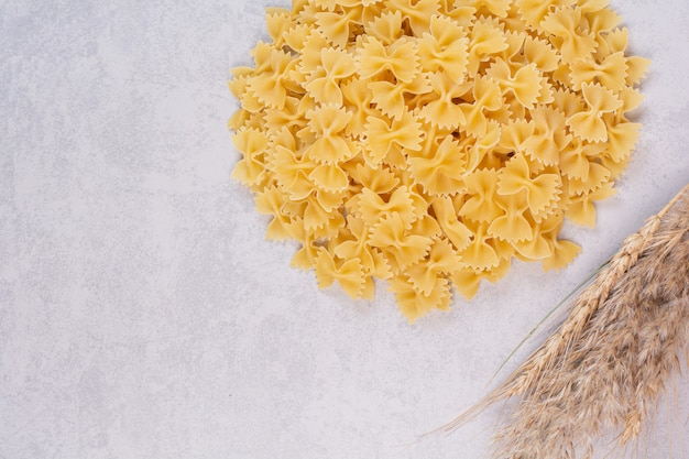 Uncooked farfalle pasta on white surface with wheat