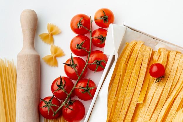Сырые феттучини, фарфалле, спагетти и помидоры