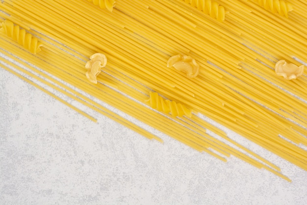 Сырые свежие макароны на белом пространстве