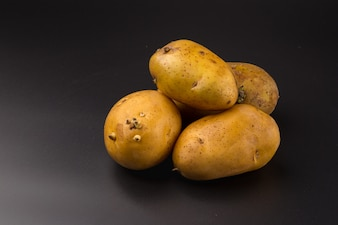 Uncooked fresh potatoes isolated on a Black background