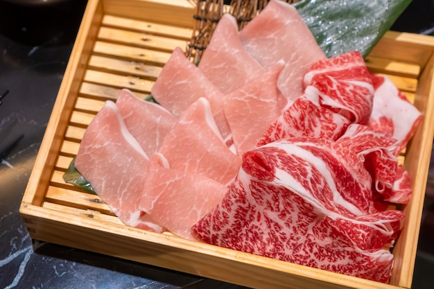 Uncooked fresh sliced pork and beef put in a wooden square box that preparing for shabu