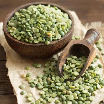 나무 테이블에 숟가락으로 그릇에 생 쌀된 녹색 분할 완두콩