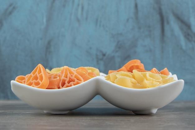 Сырые макароны в форме сердца и банта на белой тарелке