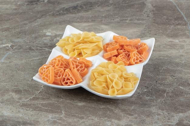 Сырые макароны в форме сердца и банта на белой тарелке.