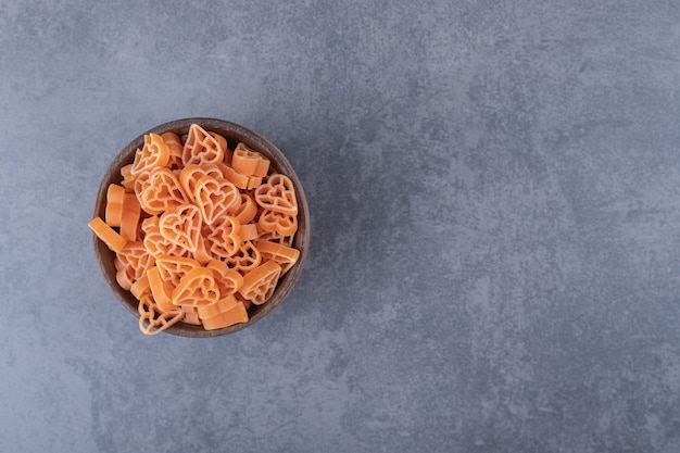 Сырые макароны в форме сердца в деревянной миске.