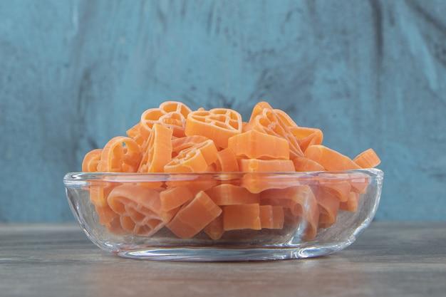 Сырые макароны в форме сердца в стеклянной посуде.