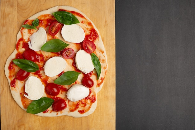 Uncooked homemade pizza on cutting board on dark background