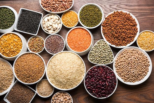 木製の表面上の白いボウルに未調理のインドの豆類、穀物、種子。セレクティブフォーカス
