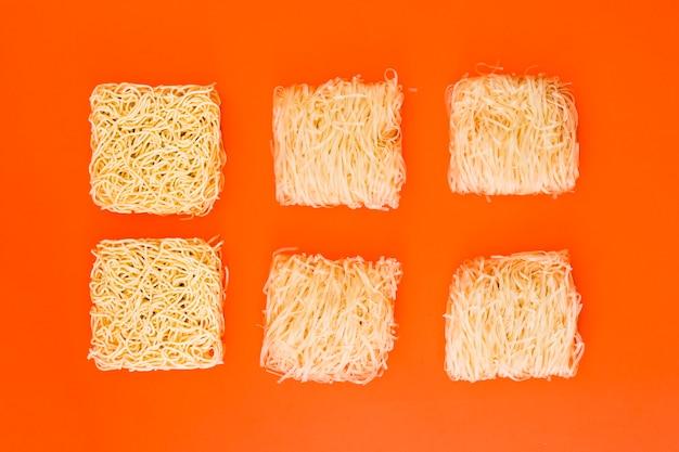 Uncooked instant noodles arranged over orange surface