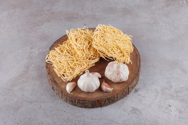 Uncooked instant noodles with fresh garlic on a wooden piece.