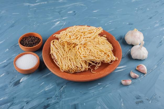 Spaghetti istantanei crudi con garlics fresco e spezie su un tavolo blu.