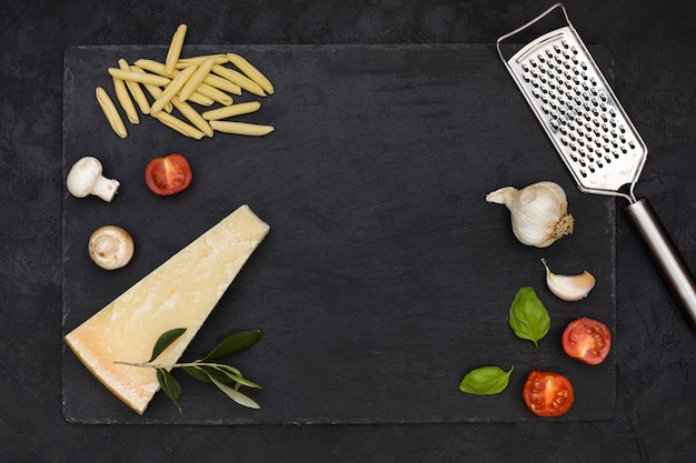 Uncooked italian garganelli pasta with ingredients and cheese grater on rock slate against black backdrop