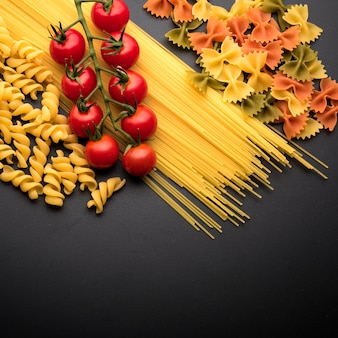 Uncooked italian pasta and cherry tomatoes over kitchen worktop