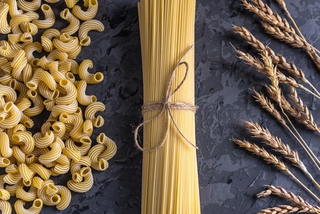 Uncooked italian pasta spaghetti and cavatappi with spikelets of durum wheat