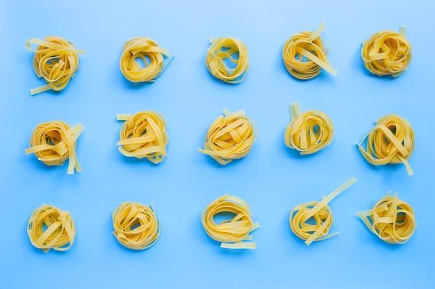 Сырые итальянские макароны тальятелле гнездо на синей поверхности