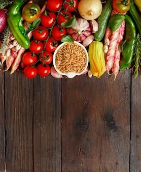 木の上に野菜と未調理のカムット穀物