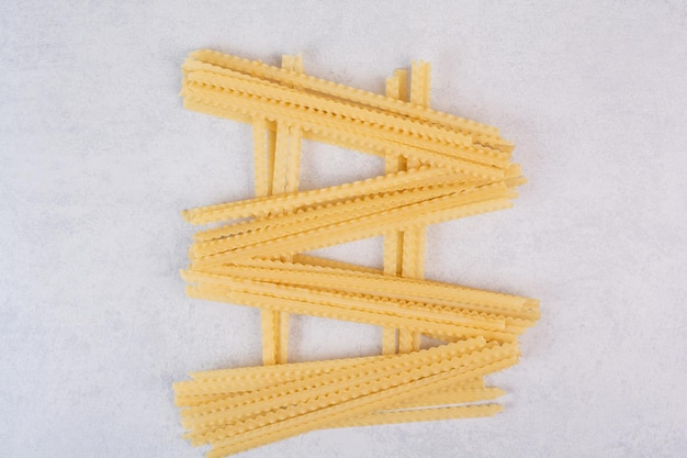 Uncooked long pasta on marble table.