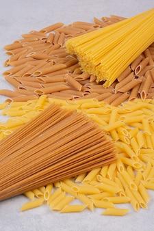 Maccheroni crudi con pasta fresca cruda su uno spazio bianco.