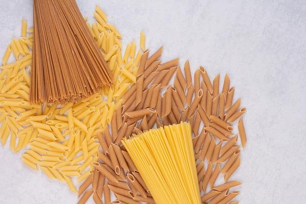Maccheroni crudi con pasta fresca cruda sulla superficie bianca