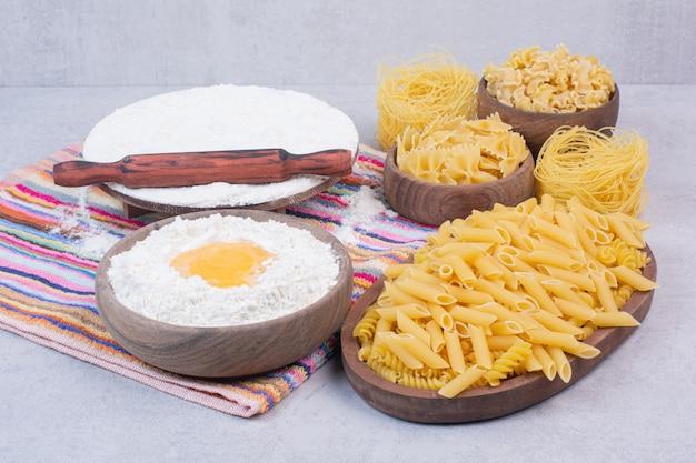 Maccheroni crudi su ciotole di legno con tuorlo e farina