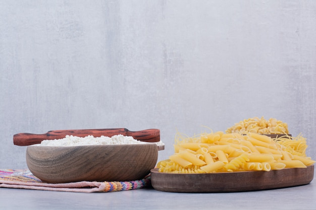 Uncooked macaroni on wooden bowls with yolk and flour