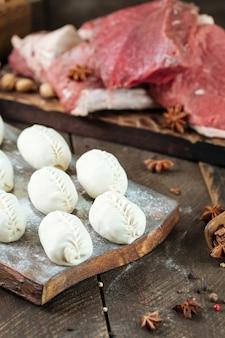 생 쌀된 맨티. 고기와 양파와 함께 중앙 아시아 전통 만두 고기 요리. 준비되지 않은 원시.