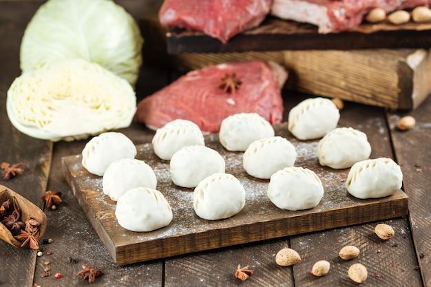 Сырые манты. среднеазиатские традиционные пельмени мясное блюдо с мясом, капустой и луком.