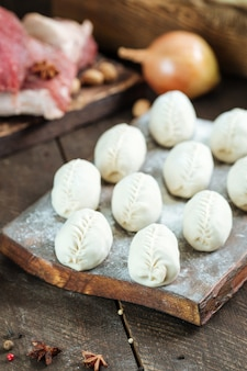 Сырые манты. среднеазиатское традиционное мясное блюдо с мясом и луком.