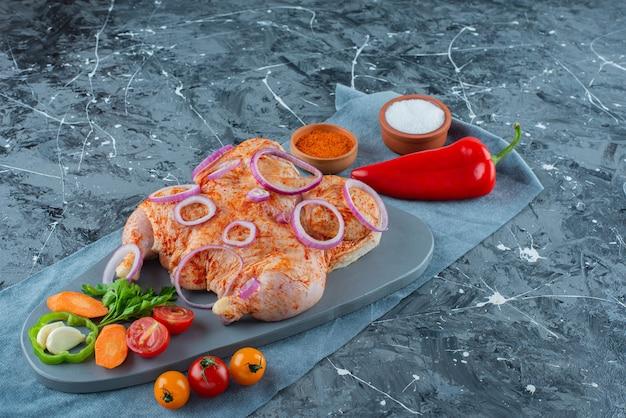Сырой маринованный цыпленок с овощами на доске на кусках ткани, на синем фоне.