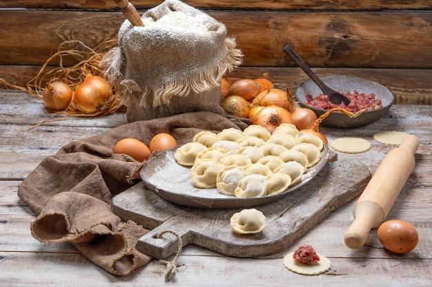 Uncooked meat dumplings - russian pelmeni on cutting board