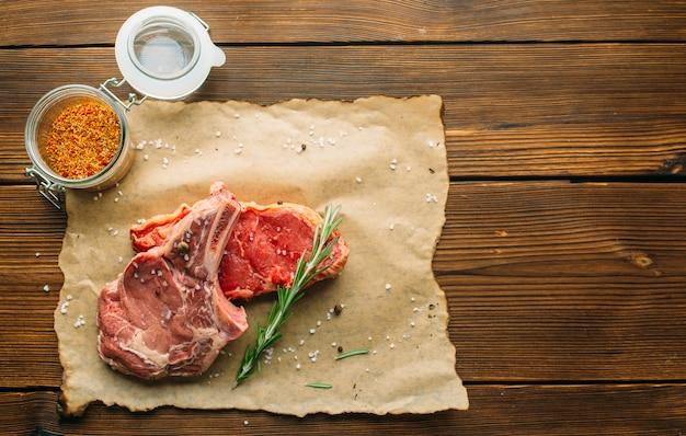 Сырое мясо в приправах на деревянном столе, вид сверху